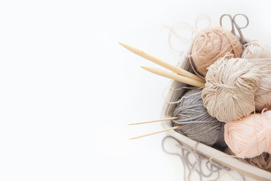 Neutral beige yarn for knitting is in the basket. Knitting needles, scissors. White background.