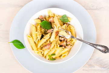 Italian food - pasta with pancetta, parmesan cheese and basil on a plate close-up, top view.