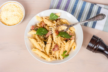 Traditional dish of Italian cuisine - penne pasta with pancetta, parmesan cheese and basil on a plate close-up, top view