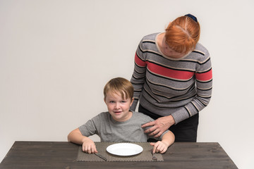 Portrait of a boy child on a white background at the table with a plate with mom.