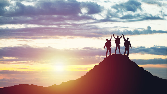 Silhouettes of happy three people on top of a mountain