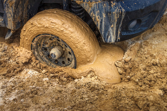The wheel of the offroad car stuck in the wet sand ground