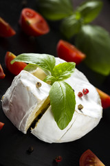 Camembert cheese with basil leaves four colors pepper and chili peppers