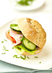 Sandwich with ham, lettuce, cucumber and tomato served on a plate. Home made food. Symbolic image. Concept for a tasty and healthy meal. Bright background.