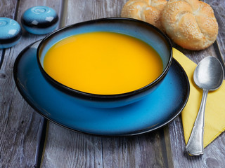 Butternut squash soup served in a blue bowl, on gray rustic background