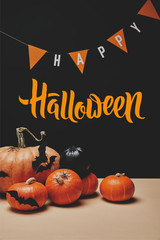 "pumpkins, paper bats and paper garland with ""happy halloween"" lettering"