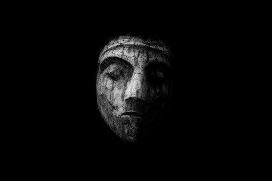 scary stone face isolated on black background