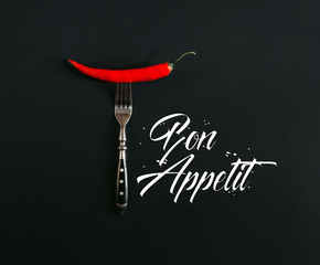 """red hot chili pepper on fork on black with """"bon appetit"""" lettering"""