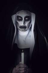 frightening evil nun with a lit candle