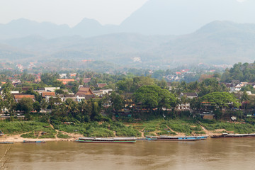 Moored boats on the Mekong River, city of Luang Prabang and mountains in the background viewed from the Chomphet District on a sunny day in Laos.