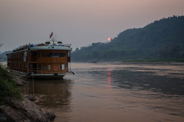 View of a moored river cruise ship on the Mekong River and Chomphet District across the river in Luang Prabang, Laos, at sunset.