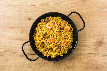 Traditional Spanish fideua. Noodle paella on wooden table. Top view.