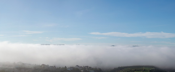 Islands in the clouds, the magic of nature with dense fog and blue sky, version panorama