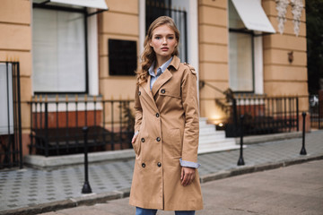 Young attractive woman in trench coat thoughtfully looking in camera while walking around cozy city street