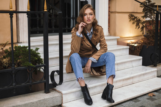 Beautiful girl in trench coat and jeans dreamily looking in camera sitting on little stairs while spending time on cozy city street
