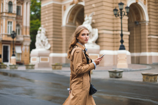 Thoughtful girl in trench coat dreamily looking in camera holding cellphone in hand while walking on cozy city street