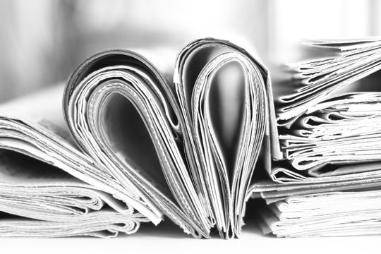 Lots of newspapers folded and stacked in pile and heart made of pages with news. Concept for reading. Stack of papers and magazines, side view, selective focus