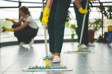 Close-up on cleaning specialist with yellow gloves holding mop while wiping floor