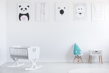 Posters on white wall in minimal kid's room interior with cradle and blue pillow on stool. Real photo