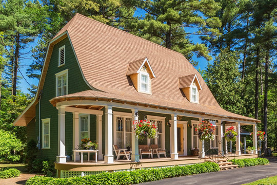 1920s house with green cedar wood shingle siding and white trim bell roof