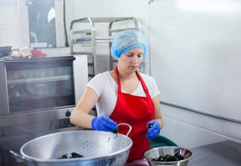 Woman preparing chillies to make jam in industrial kitchen