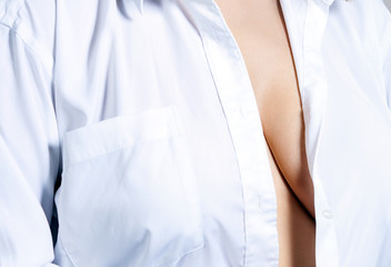 Slim woman in white shirt covering her big beautiful breast. Isolated over white