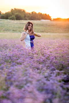 Standing girl in a white-blue dress, in a field of limonium flowers on a sunset background