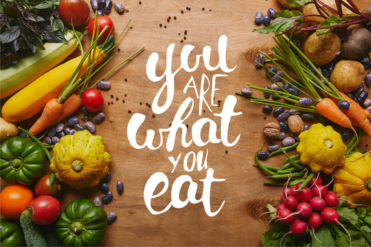 """Frame of healthy food vegetables and beans on wooden table with """"you are what you eat"""" lettering"""