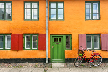 Female bicycle waiting for rider near yellow walls of historical building in traditional style of Copenhagen, Denmark. Old house on scandinavic city street