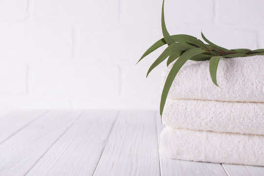 Spa composition on wooden table. Stack of three white fluffy bath towels with eucalyptus branch. Copy space