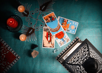 Fortune-telling on traditional tarot cards on a blue tablecloth with a lantern and candles.
