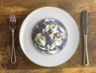 World food day concept, planet earth on plate with fork and knife on wooden table, top view
