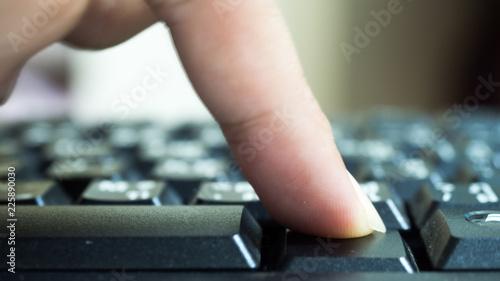 Wall mural Finger on computer keyboard keys