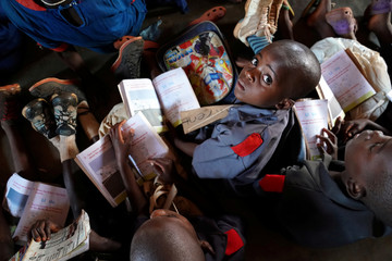 A child holds a book as U.S. first lady Melania Trump visits a school in Lilongwe