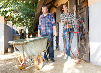 Smiling couple with barrow standing at horse stable outdoor