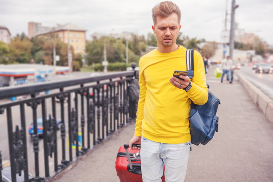 Attractive stylish young man of 30 years old with a phone in hand and a suitcase against the background of the city, navigation and travel concept