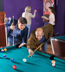 Relaxed  people playing billiard and darts