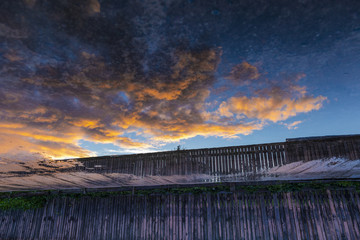 flight of burning clouds at sunset / clouds are flying above the fence and illuminated by the sunset rays of the sun