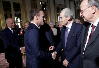 French President Emmanuel Macron greets Former President of the Constitutional Council Robert Badinter during a meeting to mark the 60th anniversary of the French Constitution at the Constitutional Council in Paris