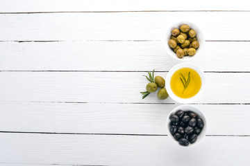 A set of olives and olive oil and rosemary. Green olives and black olives. On a white wooden background. Free space for text. Wall mural