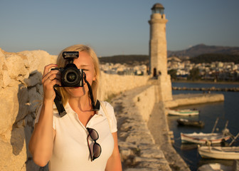 Traveler woman photographer with professional camera takes shot of Rethymno,Crete, Greece. Caucasian female photographing outdoors. Europe travel concept.