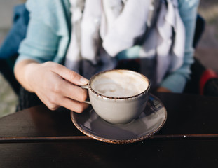 Girls hand holding coffee cup on wooden table