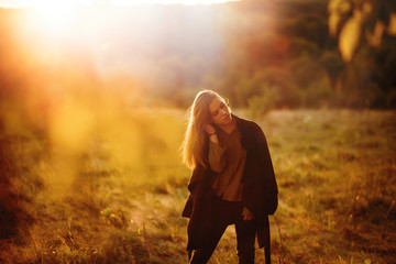 Fashion portrait of young brunette teenage girl in stylish black coat standing in the forest at golden sunset. Autumns day