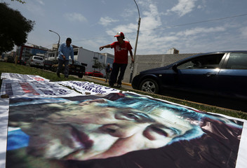 Supporters of former President Alberto Fujimori prepare a banner with a picture of him outside the Centenario hospital where he is hospitalised, after a judge annulled a presidential pardon and ordered his immediate capture and return to prison, in Lima