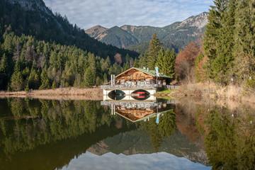 Hütte am See mit Bergen und Spiegelung, Bayern