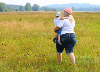 Overweight mother with her child walking together on meadows. Family enjoying life on countryside.