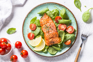 Baked salmon fish fillet with fresh salad top view.