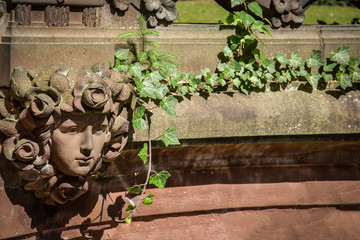 Frauenkopf in einer Steinmauer mit Efeu bewachsen