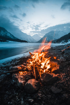 Winter campfire in the top of a frozen lake at night, a magnificent view of the mountains at sunset. Traveler's Life
