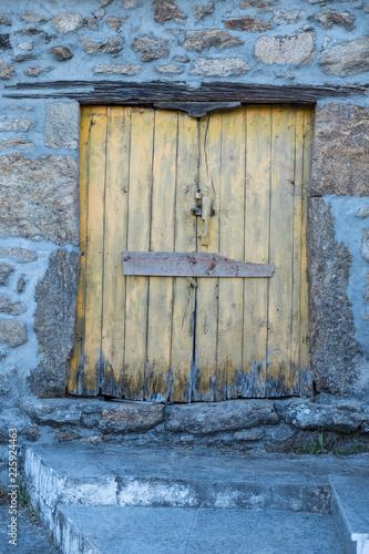 Puerta Antigua De Madera Pintada De Amarillo En Muro De Piedra